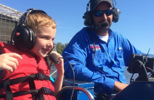 Everglades City Airboat captain next to a kid with headset