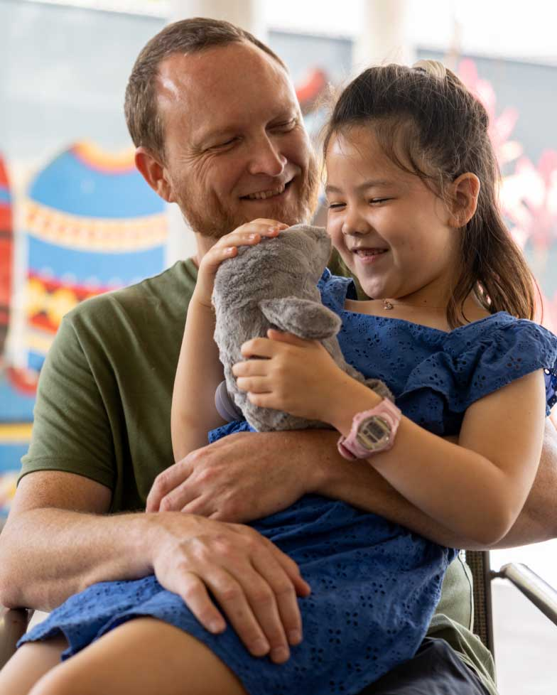 Little girl smiling with her Dad holding a stuffed animal