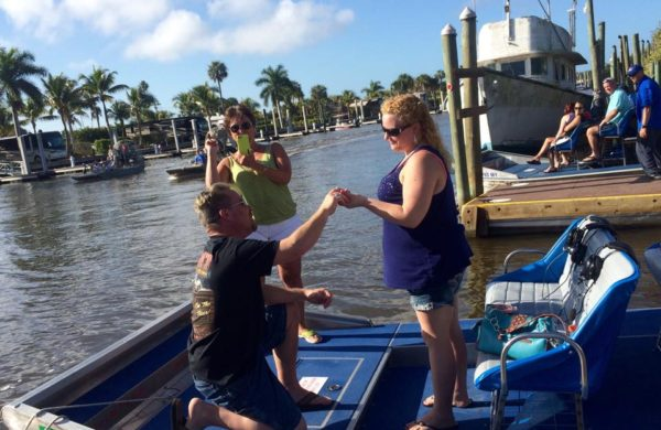 A man kneeling proposing to a woman on Everglades City Airboat Tours
