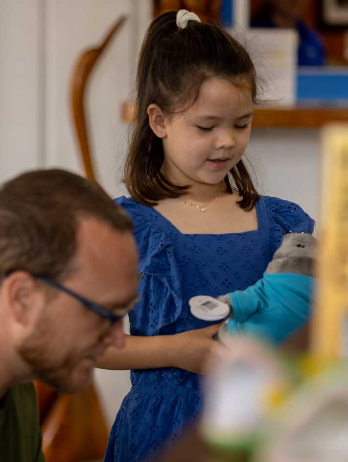 Little girl shopping a manatee stuffed animal